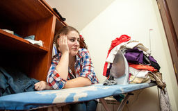 Woman looking on big pile of clothes on press board Stock Image
