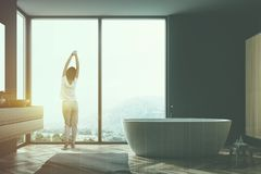 Woman in gray bathroom interior, tub and sink. Woman looking in big window of stylish gray bathroom with wooden floor, gray rug, bathtub, and sink with vertical royalty free stock image