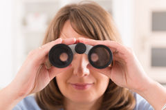 Woman looking through binocular Stock Image