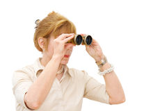 Woman looking through binoculars. In search for success - mature businesswoman looking through binoculars. Isolated over white background with room for your text royalty free stock images