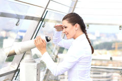 Woman looking through binoculars. Caucasian woman looking through binoculars over the city Stock Photos