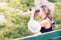 Woman looking through binoculars. Woman looking at mountains through binoculars Stock Image