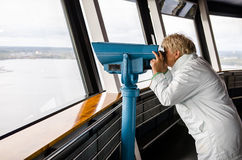 Woman looking through binoculars from Nasinneula Tower Royalty Free Stock Images