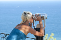 Woman looking through binoculars at sea Stock Image