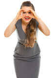 Woman looking through binoculars shaped hands Stock Images