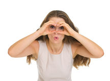 Woman looking through binoculars shaped hands Royalty Free Stock Photo