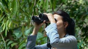Woman looking through binoculars at the trees. Enjoying the view at asian jungle. Trekking through the jungle stock video