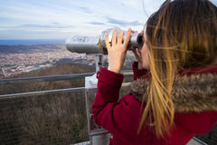 Woman Looking Through Binoculars. Young blond woman looking through binoculars at Arandjelovac town in Serbia, from mountain Bukulja Royalty Free Stock Photo