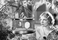 Woman looking into a bird cage with birds Royalty Free Stock Photos