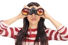 Woman looking through black binoculars royalty free stock photography