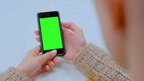 Woman looking at black smartphone device with empty green screen. Woman looking at black compact digital smartphone device with empty green screen on table at stock footage