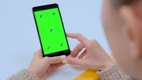 Woman looking at black smartphone device with empty green screen. Woman looking at black digital smartphone device with empty green screen on table at home stock video footage