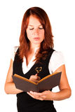 Woman looking into book. Beautiful red-headed girl is searching an old book with a magnifying glass in her hand royalty free stock photography
