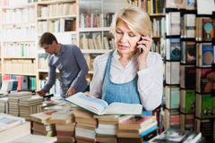 Woman looking at book and chatting on mobile phone Royalty Free Stock Image