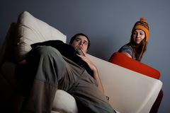 Woman looking on bored man sitting on couch royalty free stock photos