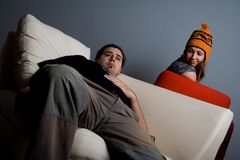 Woman looking on bored man on sofa stock images