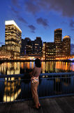 Woman Looking at Boston Skyline. Young woman looking away at boston skyline at dusk Royalty Free Stock Photo