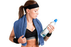 Woman Looking at a Bottle of Water. After her workout at the gym, isolated in a white background Stock Photo