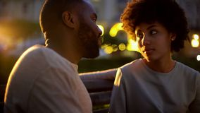 Woman looking at boyfriend with hope, outdoor date, misunderstanding, conflict stock photography