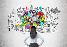Woman looking at brain and gears on concrete. Rear view of a black haired woman standing with her hands on the waist near a brain sketch with gears and a startup Royalty Free Stock Photo