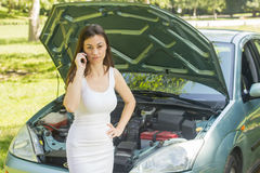 Woman looking at broken car Stock Images