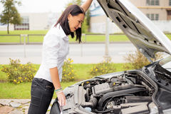 Woman looking at broken cars motor Stock Image