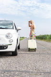 Woman looking at broken down car while pulling luggage on country road Royalty Free Stock Photos