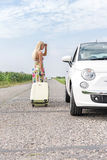 Woman looking at broken down car while pulling luggage on country road Royalty Free Stock Images