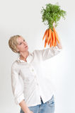 Woman looking at a bunch of carrots Royalty Free Stock Photos