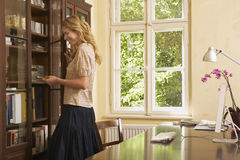 Woman Looking In Cabinet In Study Room Stock Image