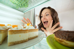 Woman Looking At Cake In Refrigerator Stock Images