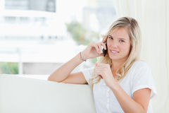 A woman looking at the camera as she talks on the phone Stock Photography