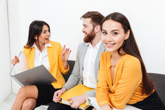 Woman looking at camera while her colleagues talking. Image of pretty women looking at camera while her colleagues sitting in office talking with each other Stock Images