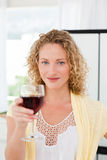 Woman looking at the camera with her drink of wine Stock Image