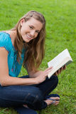 Woman looking at the camera while holding a book Stock Images