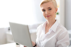 Woman looking at camera and holding laptop. Like what you do. Elegant young woman looking at the camera while standing and holding a laptop royalty free stock image