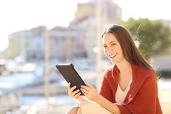 Woman looking at camera holding a tablet. Happy woman looking at camera holding a tablet in a coast town street royalty free stock image