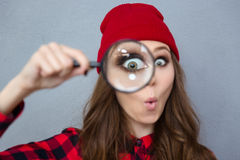 Woman looking at the camera through magnifying glass. Portrait of a funny young woman looking at the camera through magnifying glass over gray background Stock Photos
