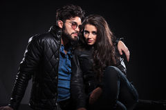 Woman looking at the camera and man looking pensive to a side. Young fashion couple on dark background, women looking at the camera and men looking pensive to a Royalty Free Stock Images