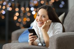 Woman looking at camera in the night holding a phone. Lying on a couch in the living room at home stock photos
