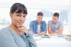 A woman looking at the camera thinking with her friends studying. A thinking women looking at the camera as her friends study behind her Royalty Free Stock Image