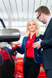 Woman looking at car in auto Royalty Free Stock Photography