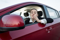Woman looking in car side mirror and applying lipstick Stock Image