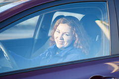Woman looking through the car side window glass. With curly hair Royalty Free Stock Photography