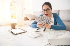 Woman looking at cash feel surprised. Portrait of happy excited successful young business woman holding money dollar bills and looking at cash feel surprised Stock Images