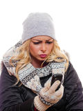 Woman looking at cell phone frowning. A attractive woman is dressed for winter looking at cell phone frowning royalty free stock images