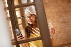 Woman looking on cell phone by window Royalty Free Stock Photo