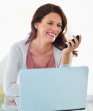 Woman looking at cellphone with laptop in front Stock Image