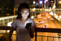 Woman looking at cellphone at night with the background of traff. Ic road ,asian young woman Royalty Free Stock Image