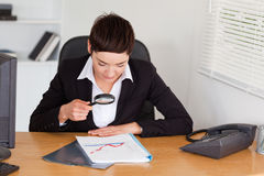 Woman looking at a chart with a magnifying glass Stock Photos